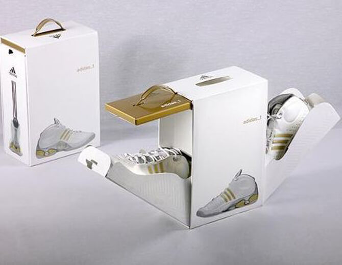 two white custom shoe box one opened with pair of white sneakers visible