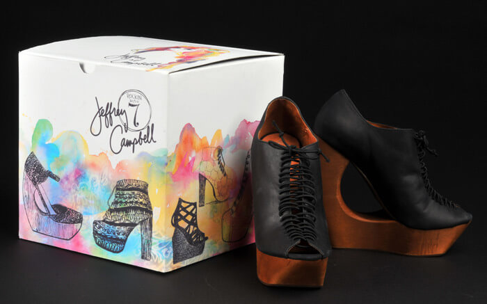 white cubed shaped shoe box with water colour design and pair of black heels displayed next to the box