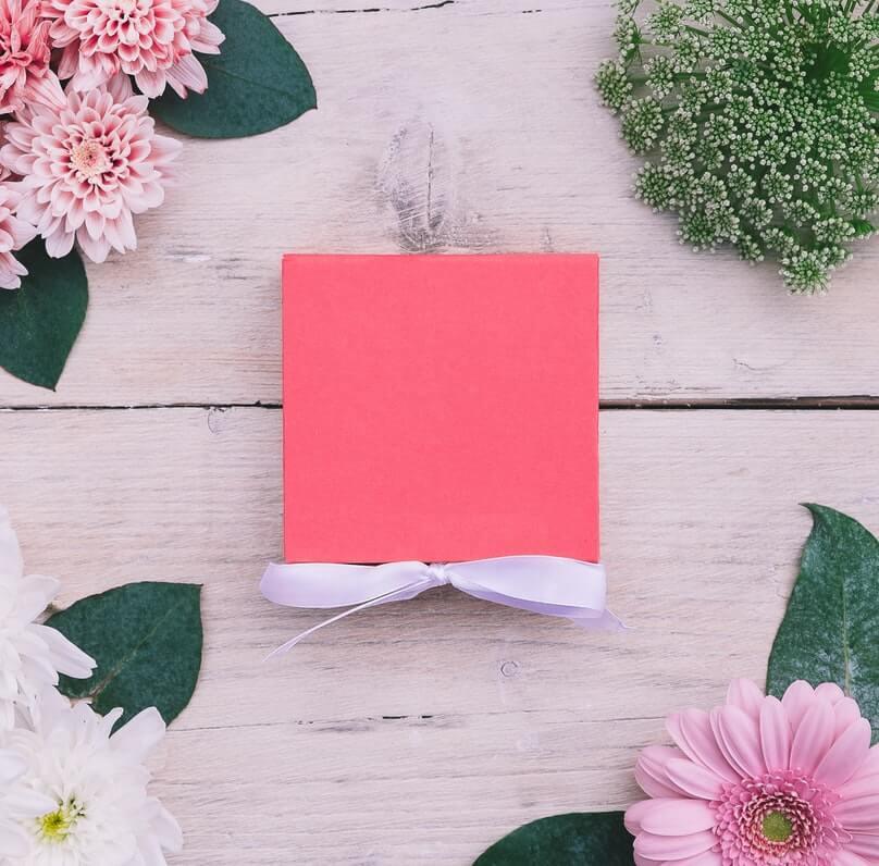 Scatola rosa fluo con fiocco e fiori