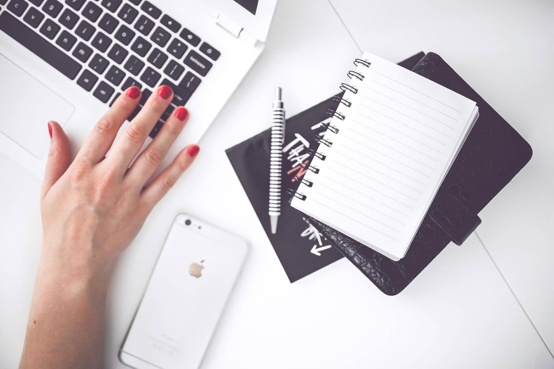 Bureau avec un ordinateur, un carnet de notes et un iPhone