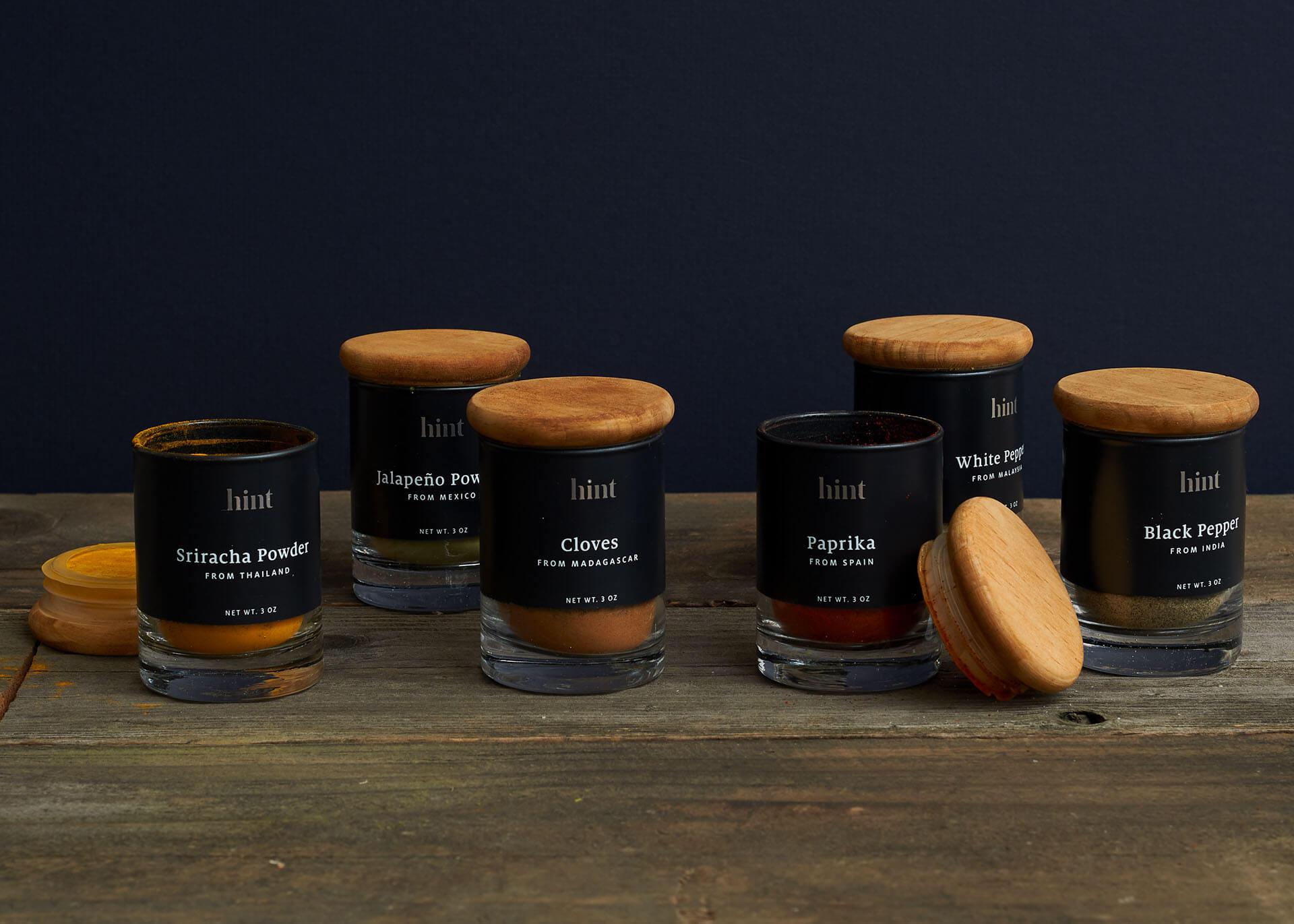 Épices de Hint, dans leur emballage noir avec un couvercle en bois