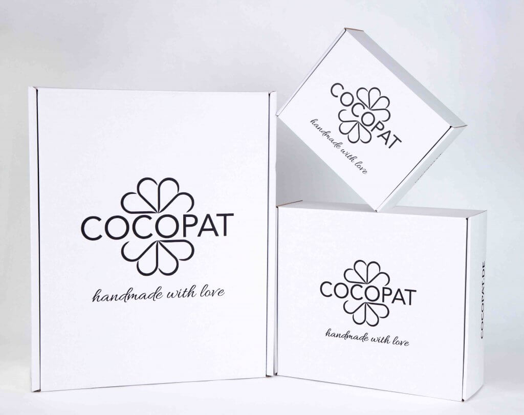 white cardboard Cocopat boxes with dark print on top