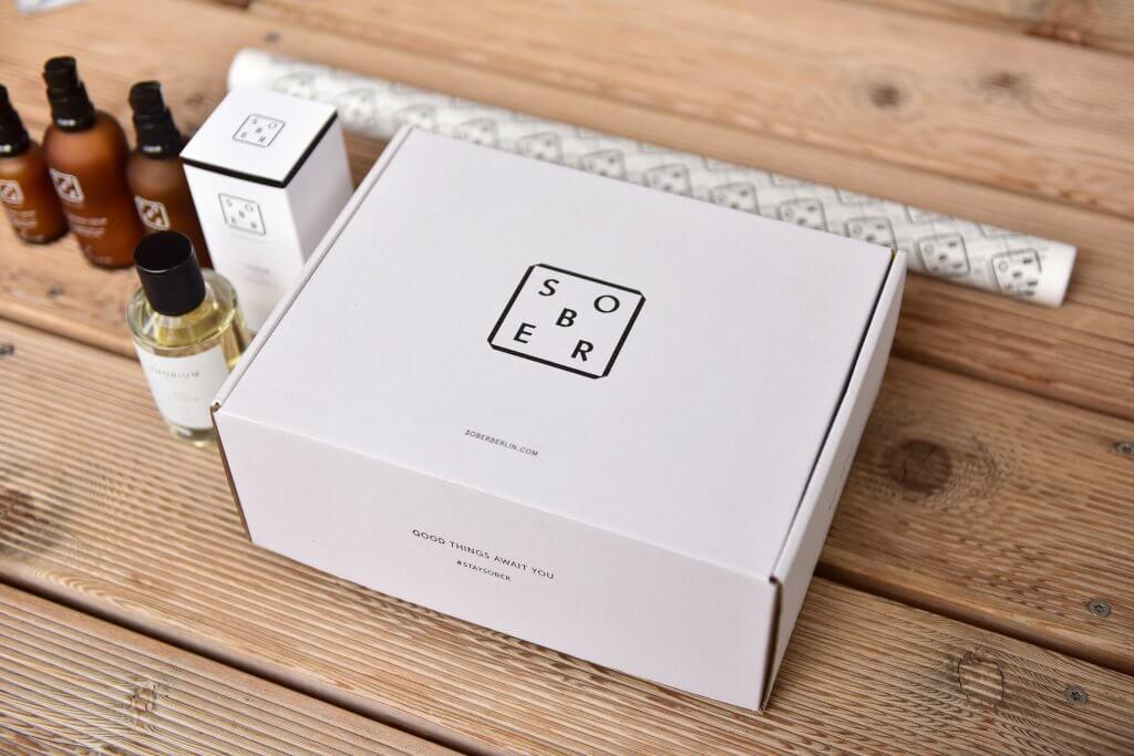 Produkte von Sober stehen neben der mit dem Logo bedruckten Verpackung - man sieht die Verpackung von der Seite