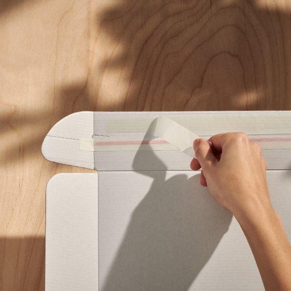 Samolepicí proužek na doručovací krabici