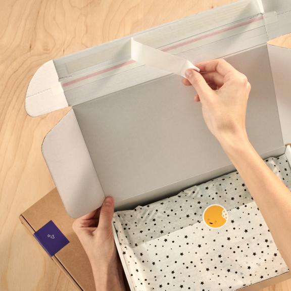 E-Commerce Versandbox, einer der beiden Klebestreifen wird abgezogen