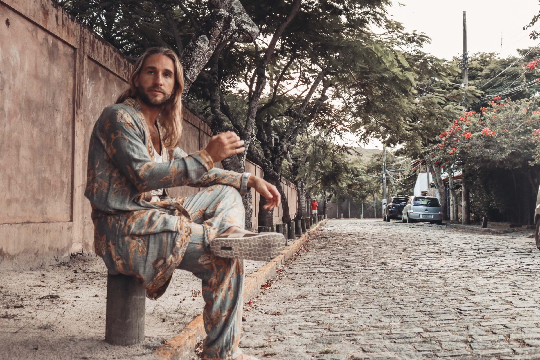 Mann in Brahmaki gekleidet sitzt und trinkt Tee.