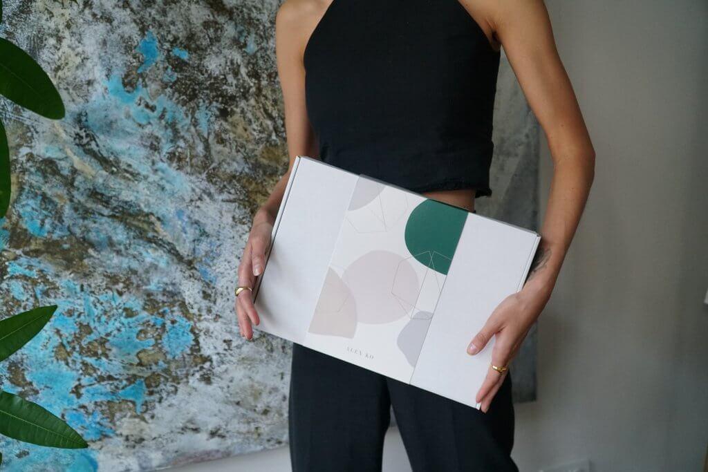 Model trägt Verpackung von Alex Ko in den Händen