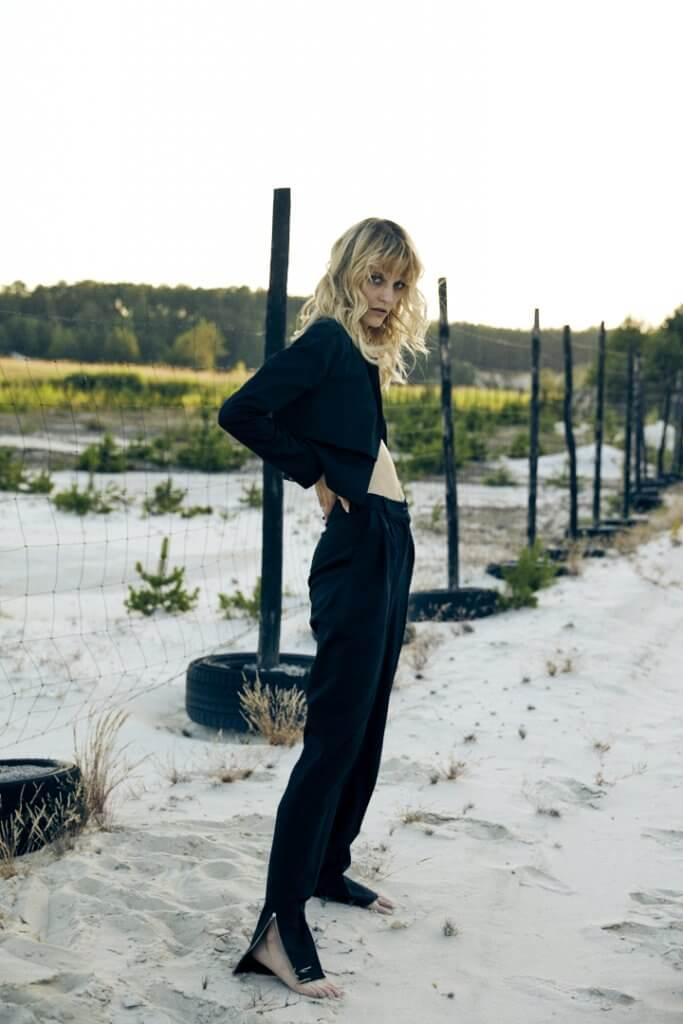 Model mit Kleidung von Alex Ko vor einem Zaun