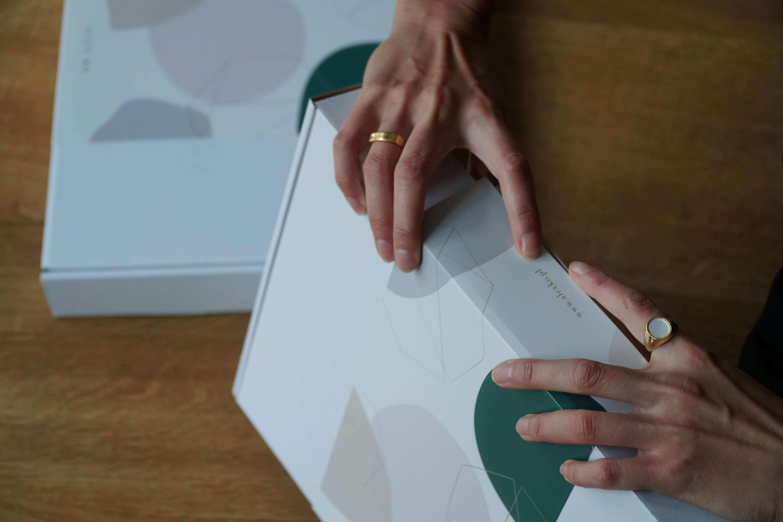 una chica sostiene una caja de cartón blanca