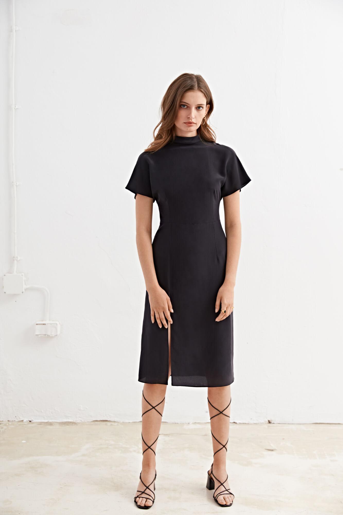 Modella in piedi con vestito nero
