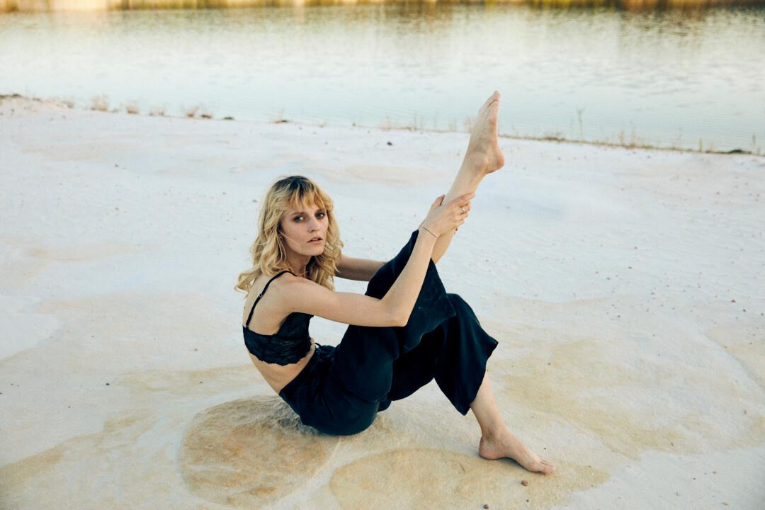Modella con top e pantalone nero sfondo lago