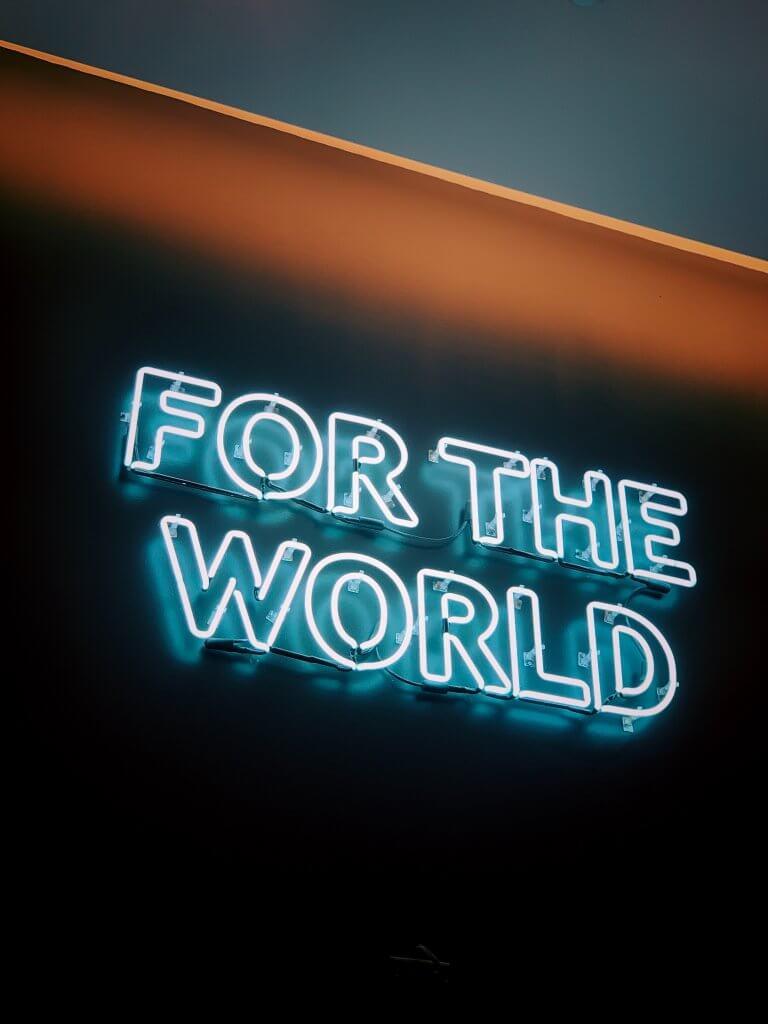 Ein Neonschriftzug der sagt: For the World - für einen Umweltfreundlichen Versand