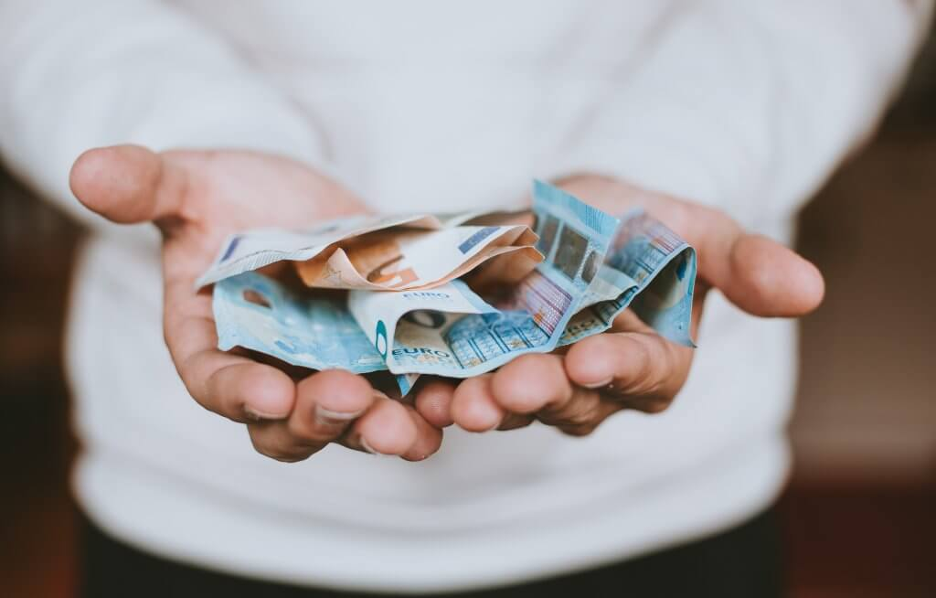 Eine Person hat ein paar Euro Scheine in der Hand um damit den Versand zu bezahlen