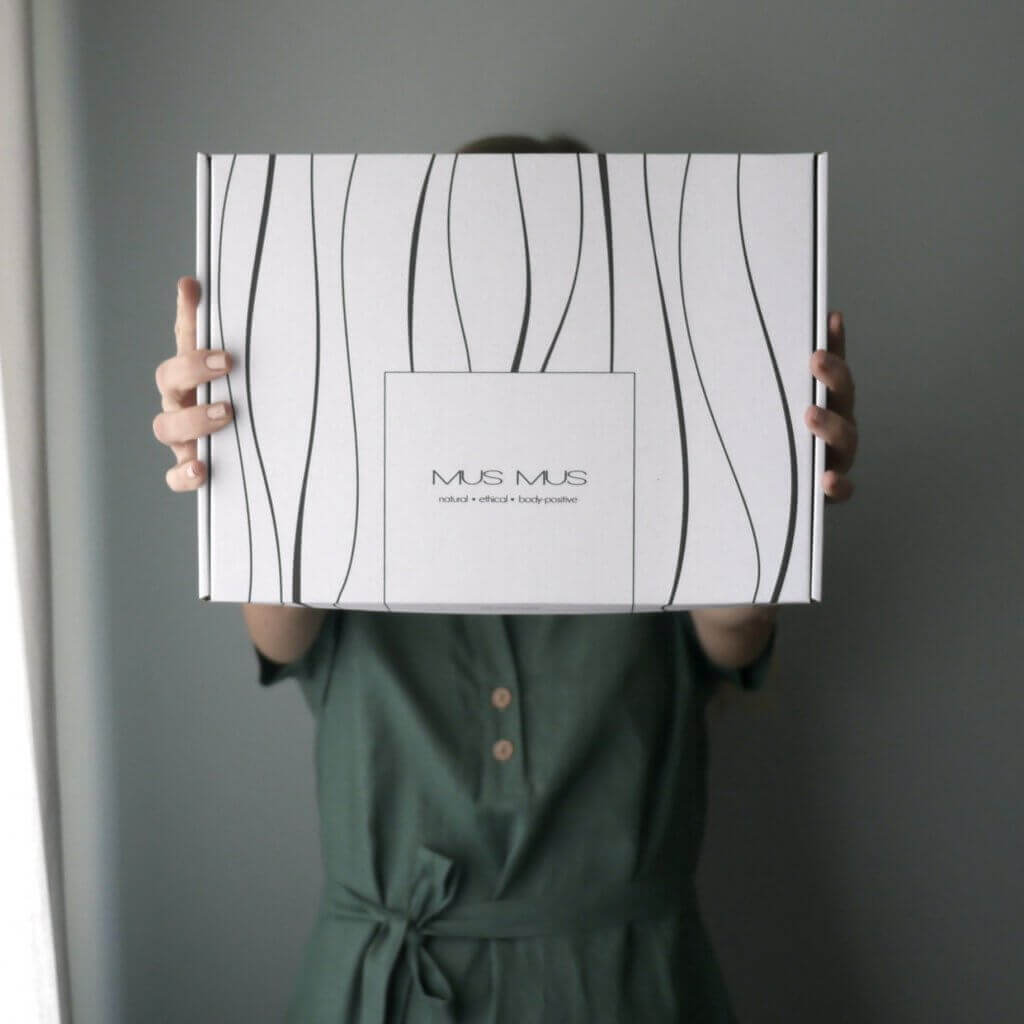una chica sostiene una caja blanca de Mus Mus