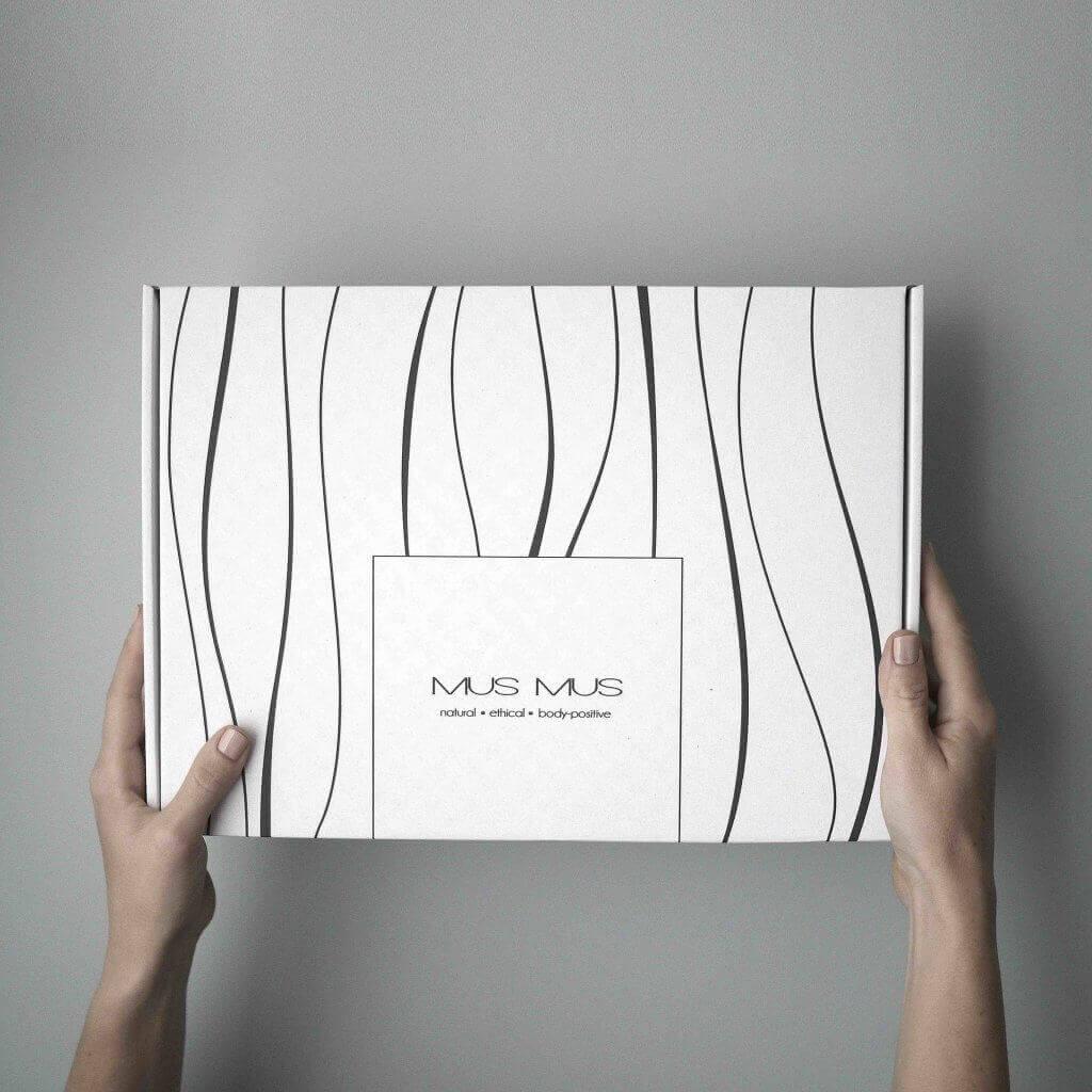 dos manos sostienen una caja blanca de Mus Mus