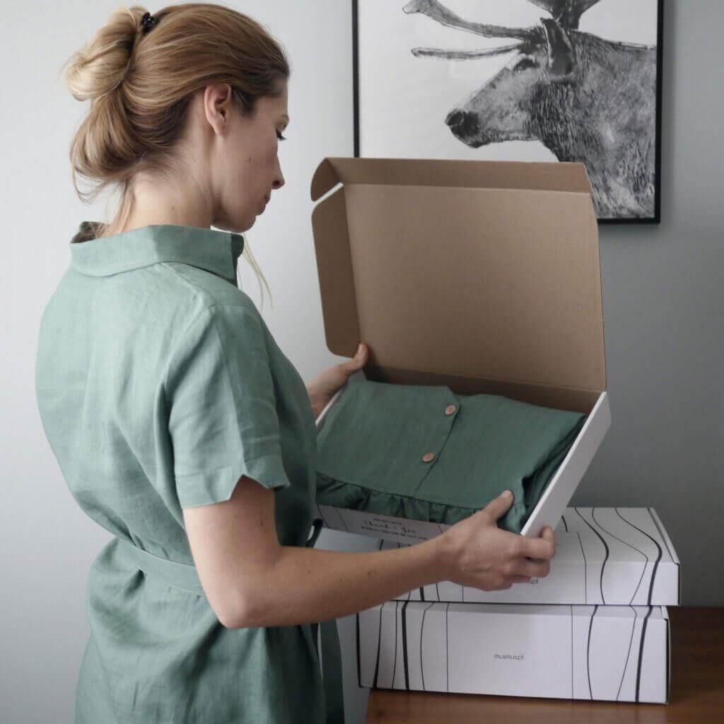 la fundadora de Mus Mus sostiene una caja con ropa