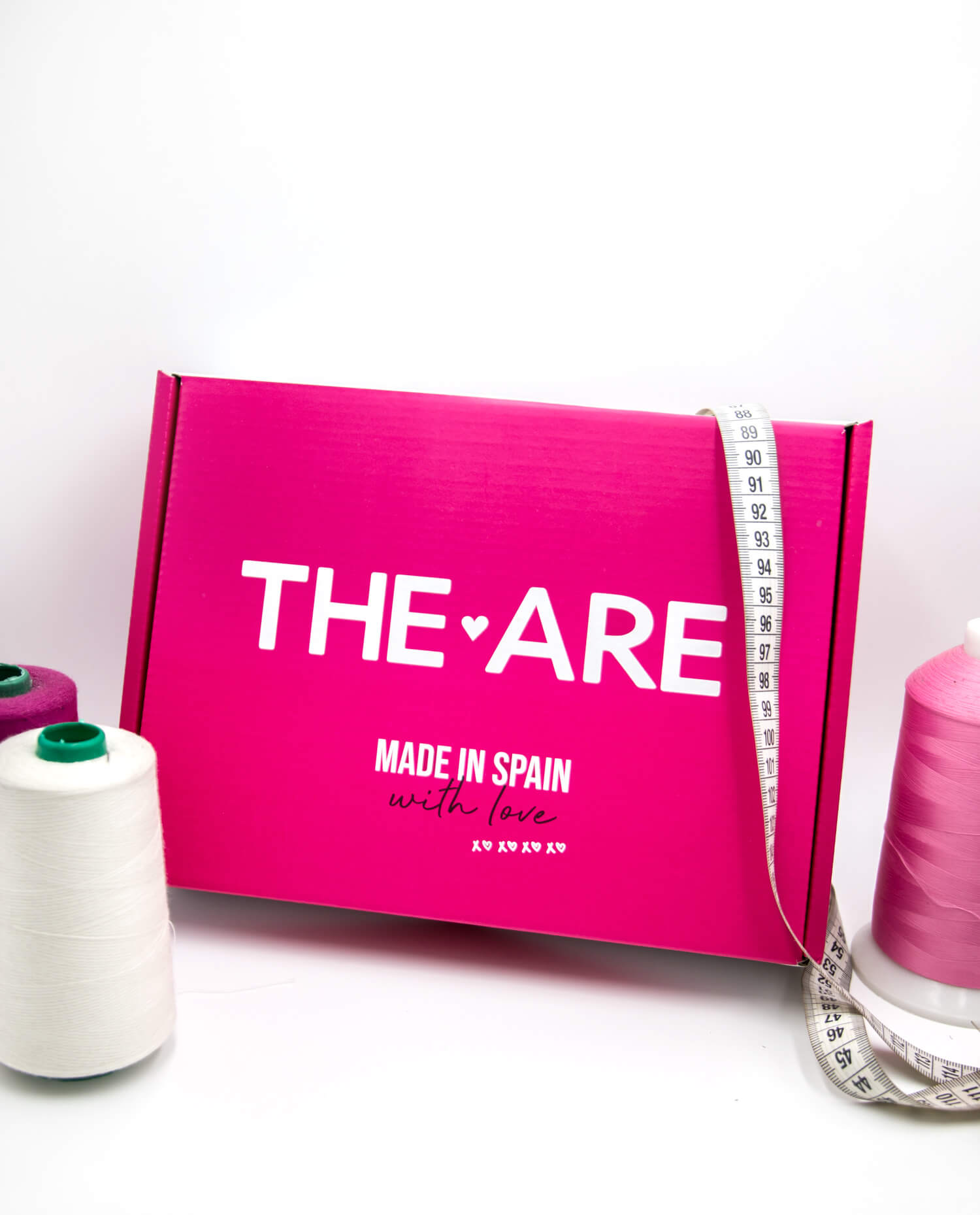 una caja de cartón rosa junto a bobinas de hilo