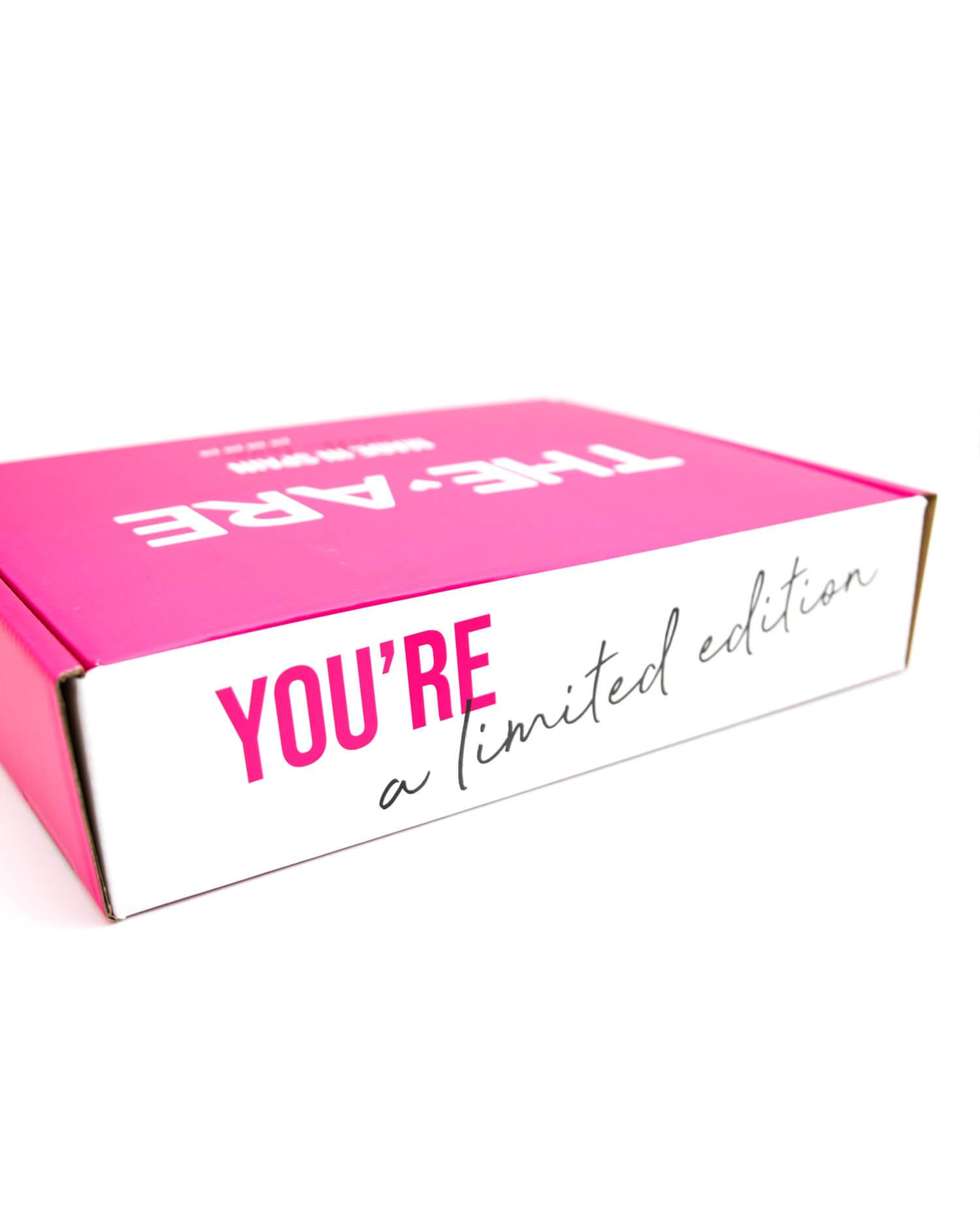 una caja rosa y blanca con una frase impresa