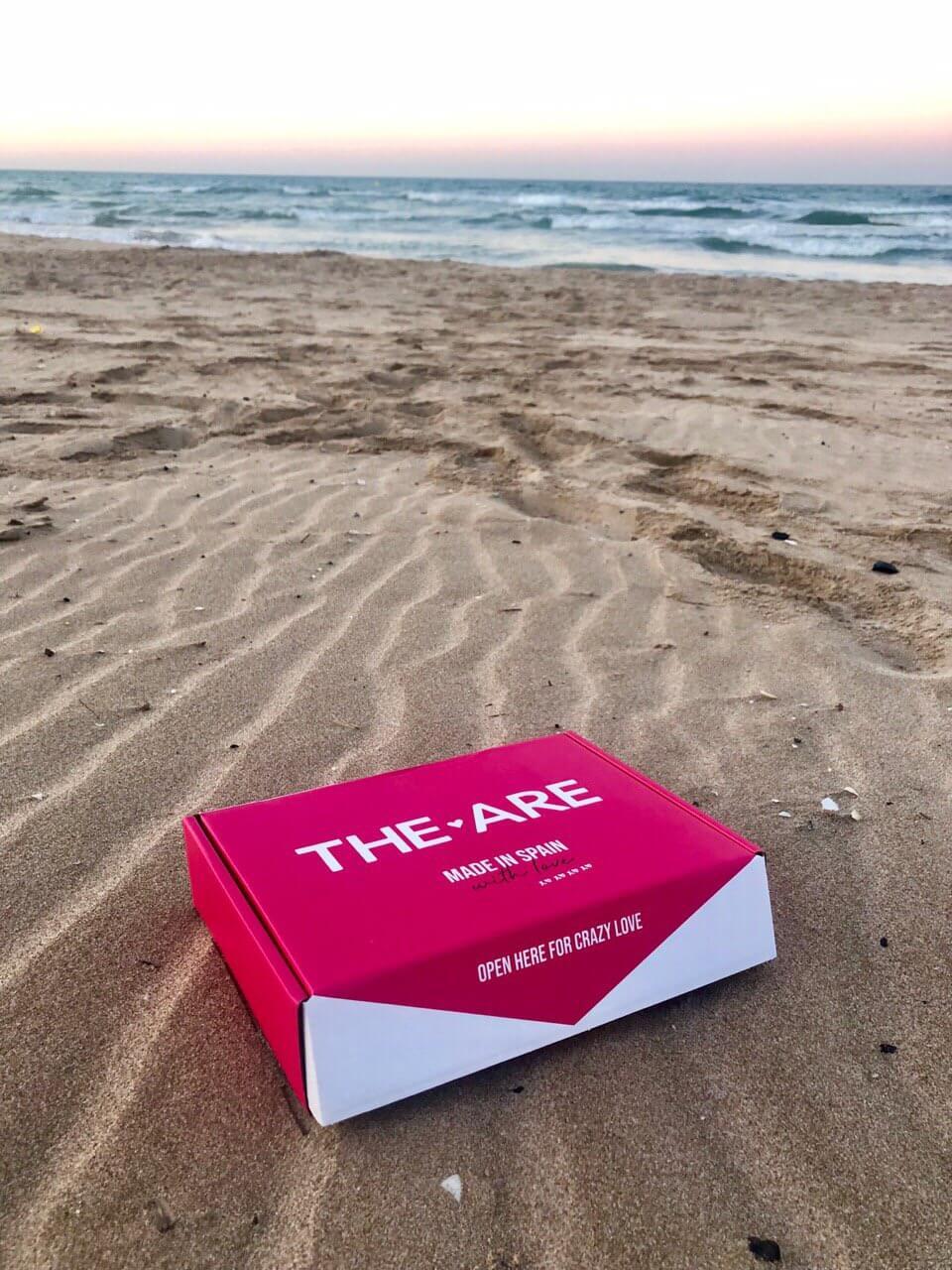 una caja de la marca THE ARE frente a la playa