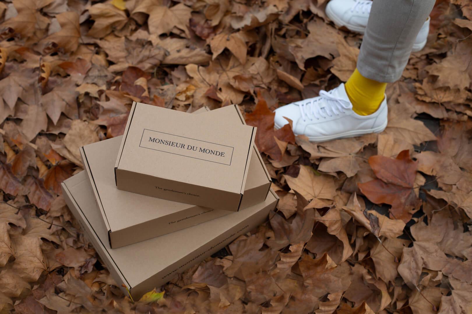 Personne en baskets à côté des boîtes Monsieur du Monde