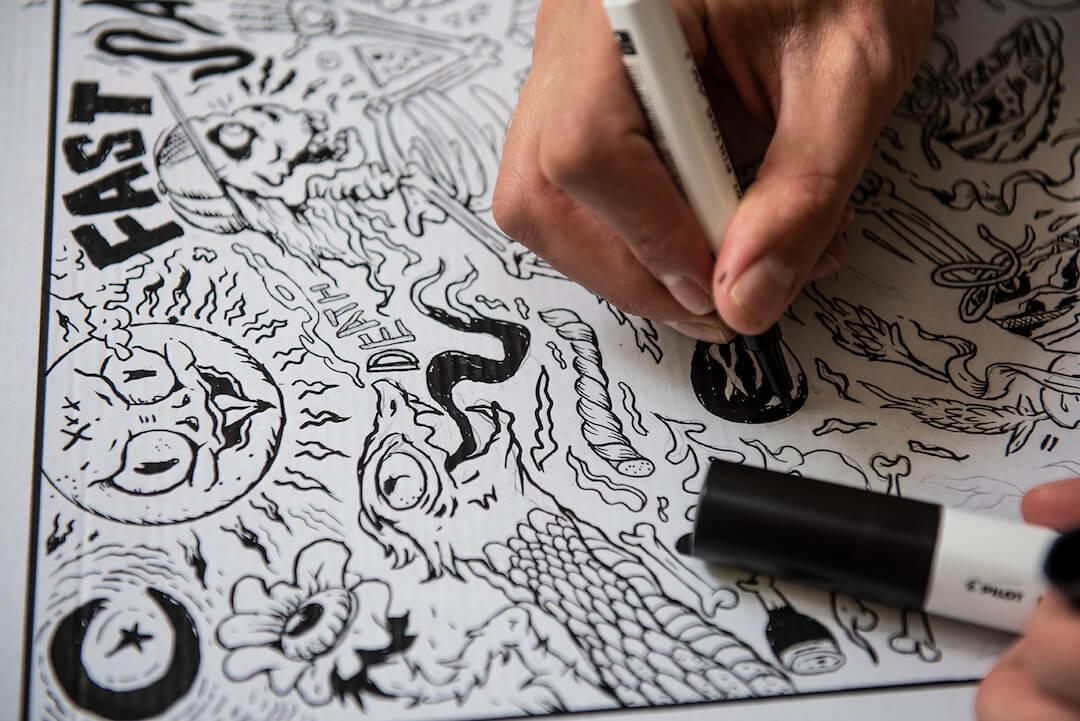Personne dessinant un motif sur une boîte de packaging Saucony