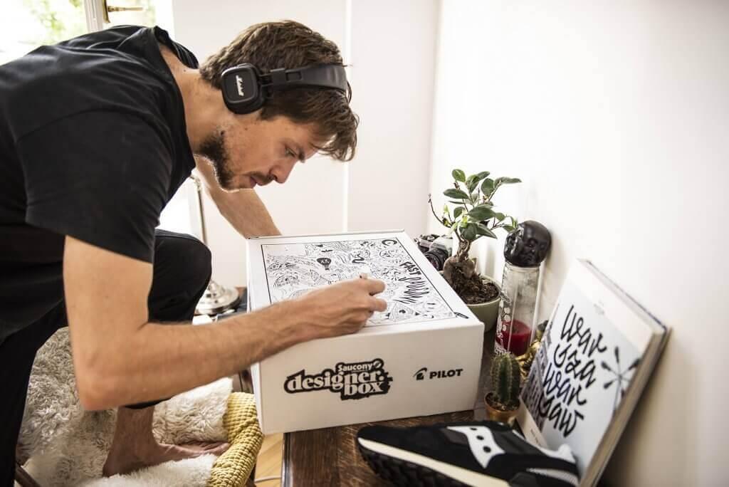 El diseñador de Saucony dibuja sobre una caja postal