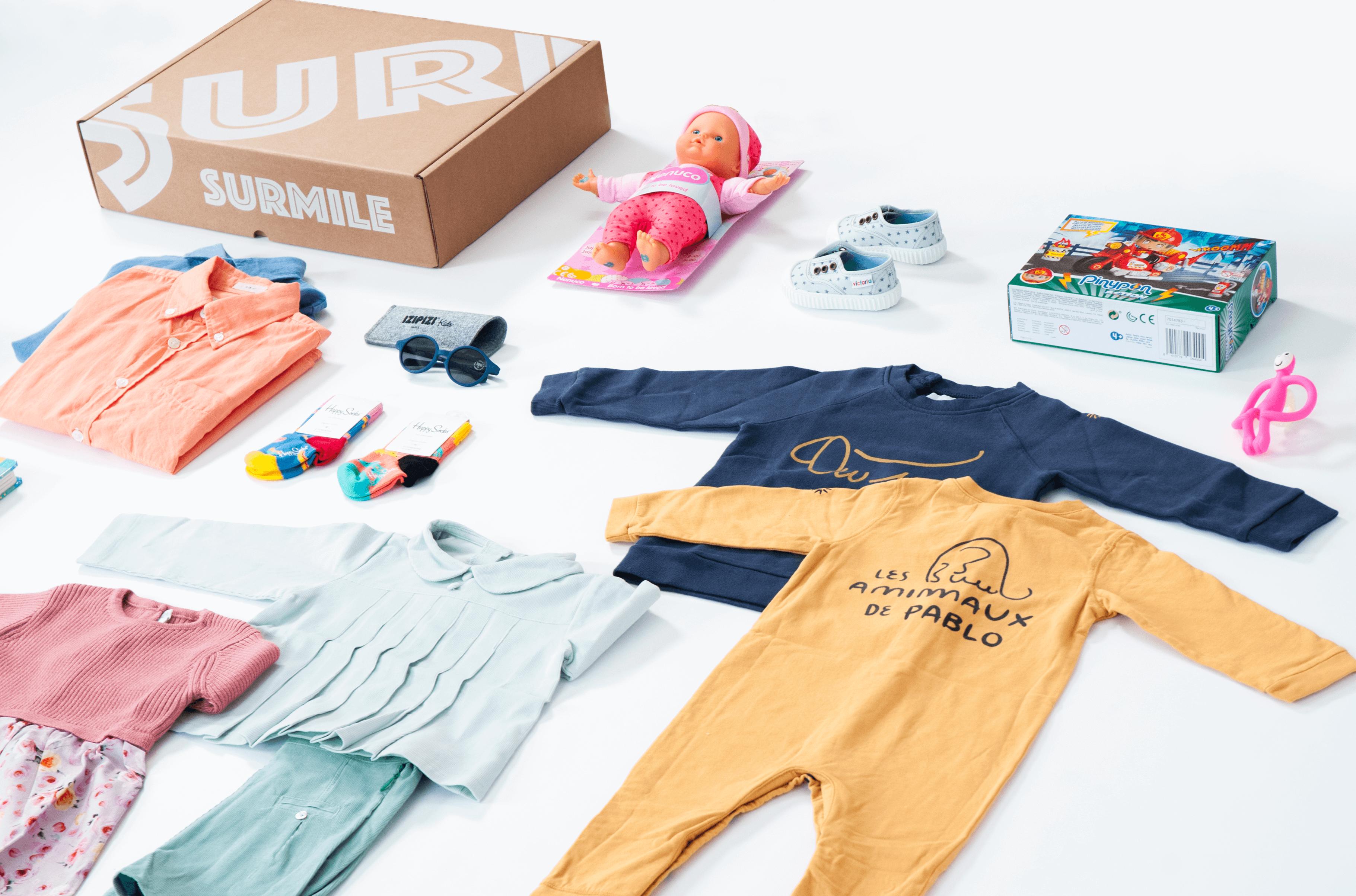 Caja de cartón de Surmile junto a varias prendas de ropa para niños