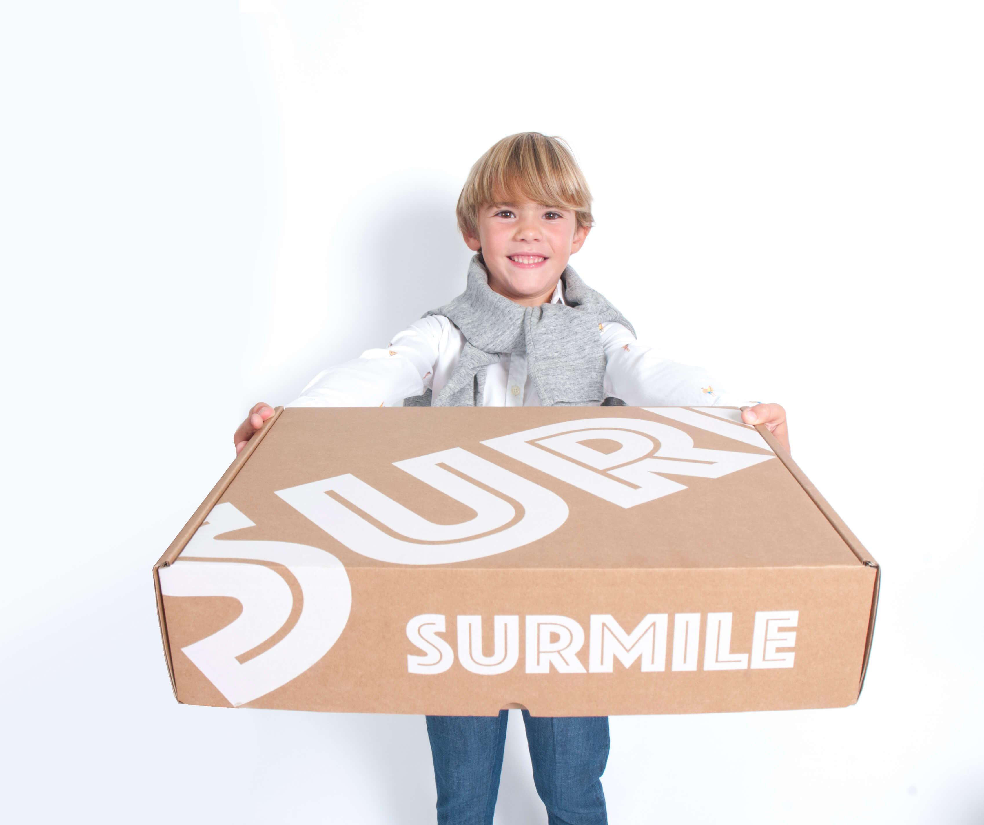 un niño sostiene una caja de Surmile