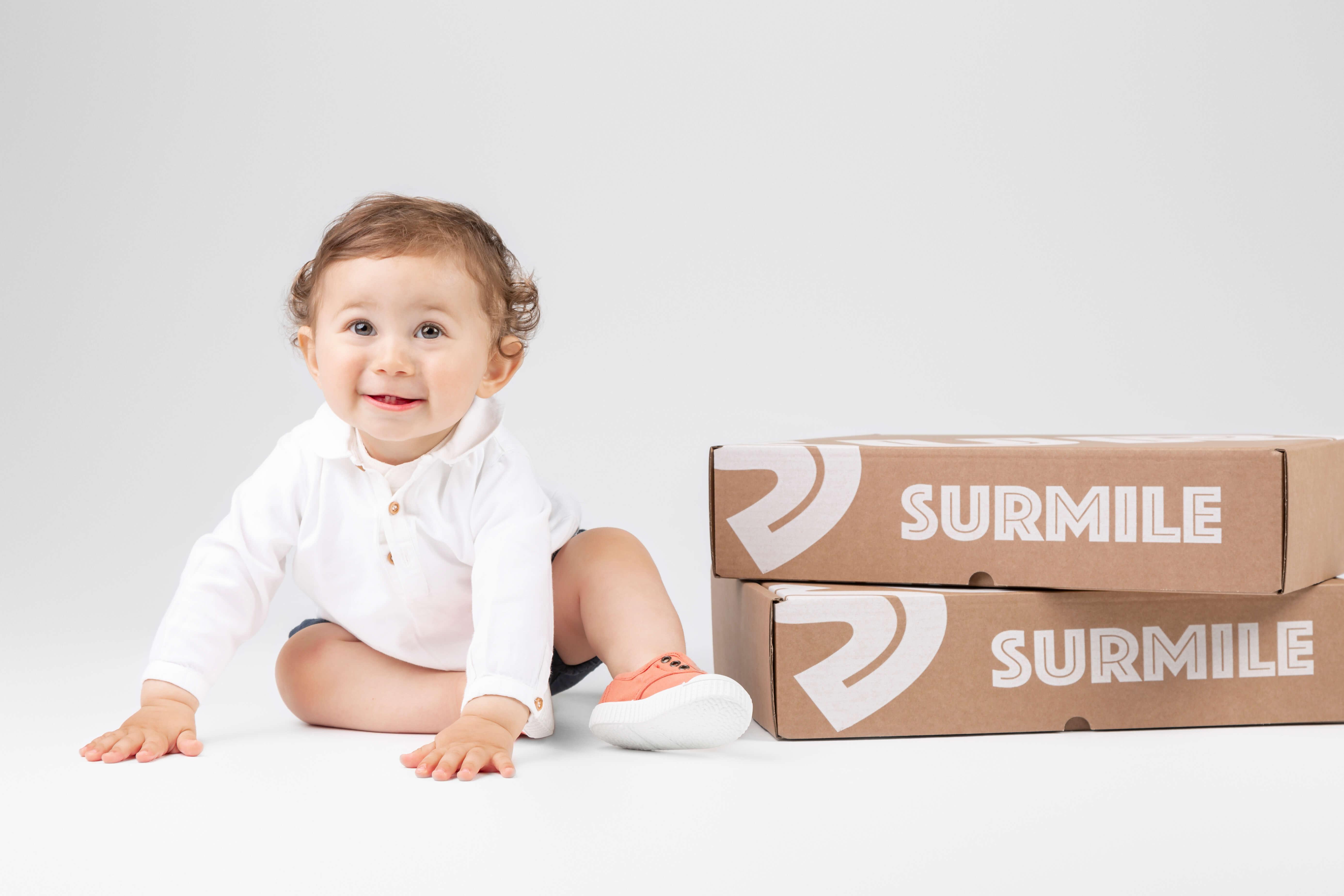 un bebé sonriente junto a una caja de cartón de Surmile