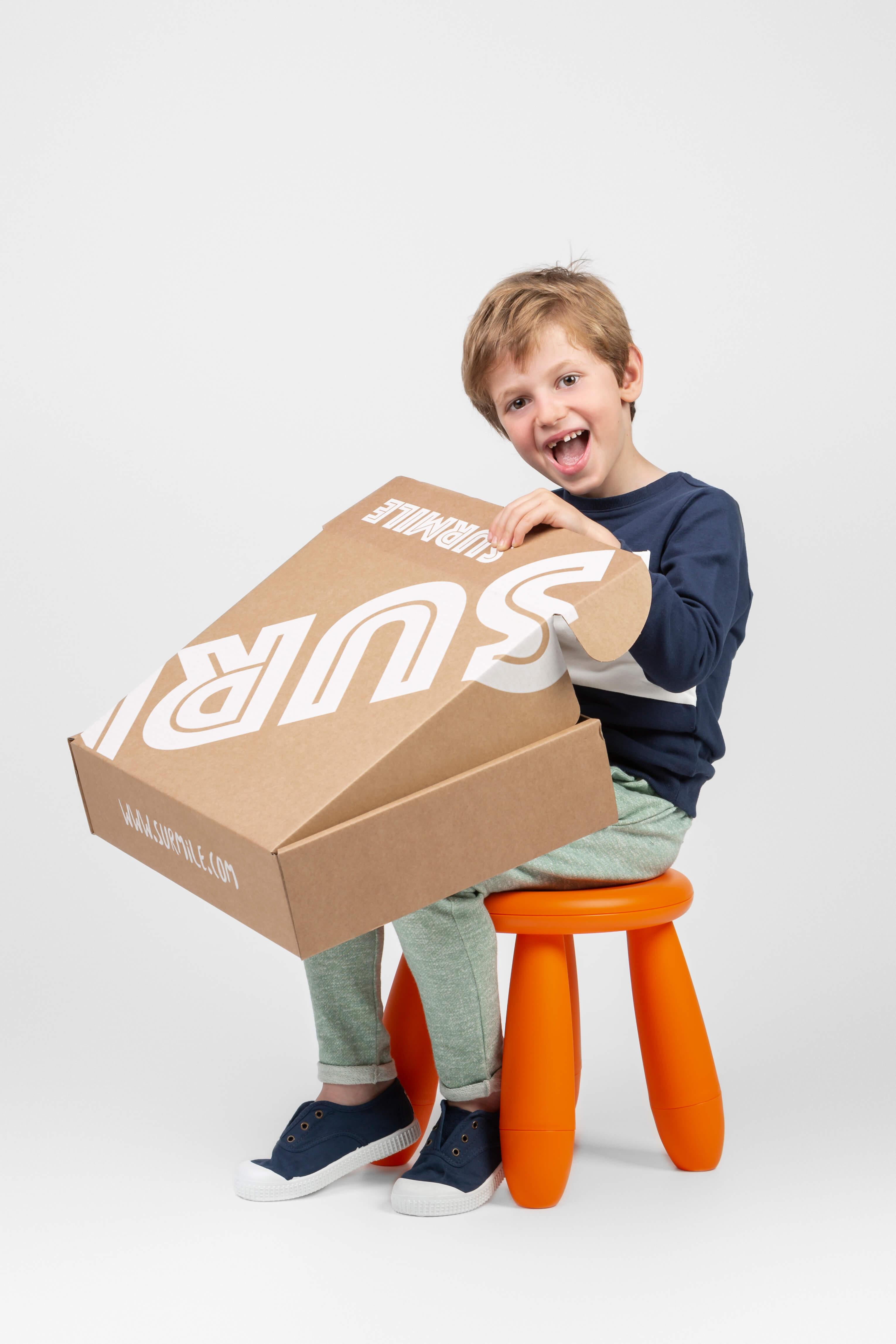 un niño muy feliz sostiene una caja de Surmile
