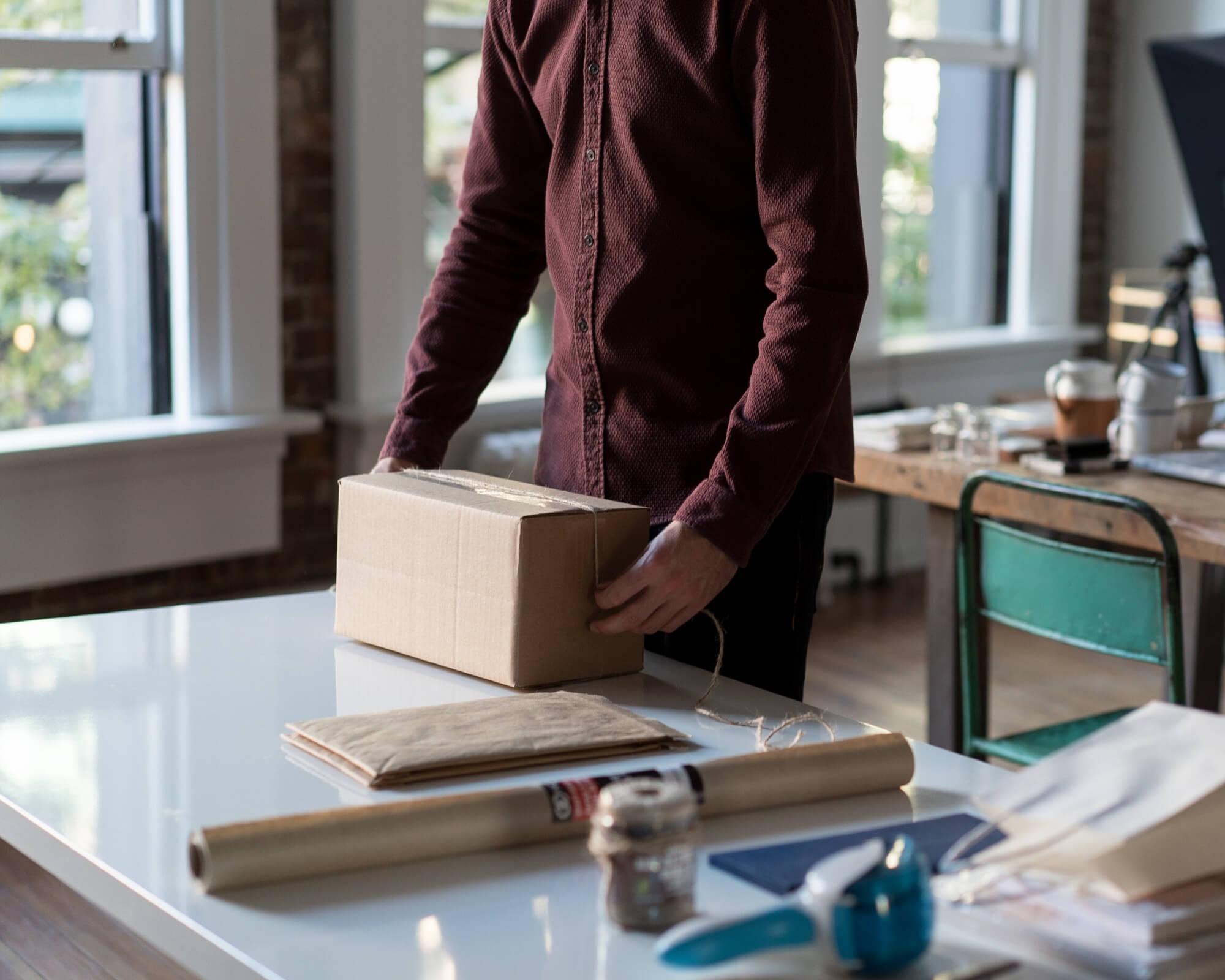 un chico monta una caja de cartón y piensa cómo reducir gastos en packaging