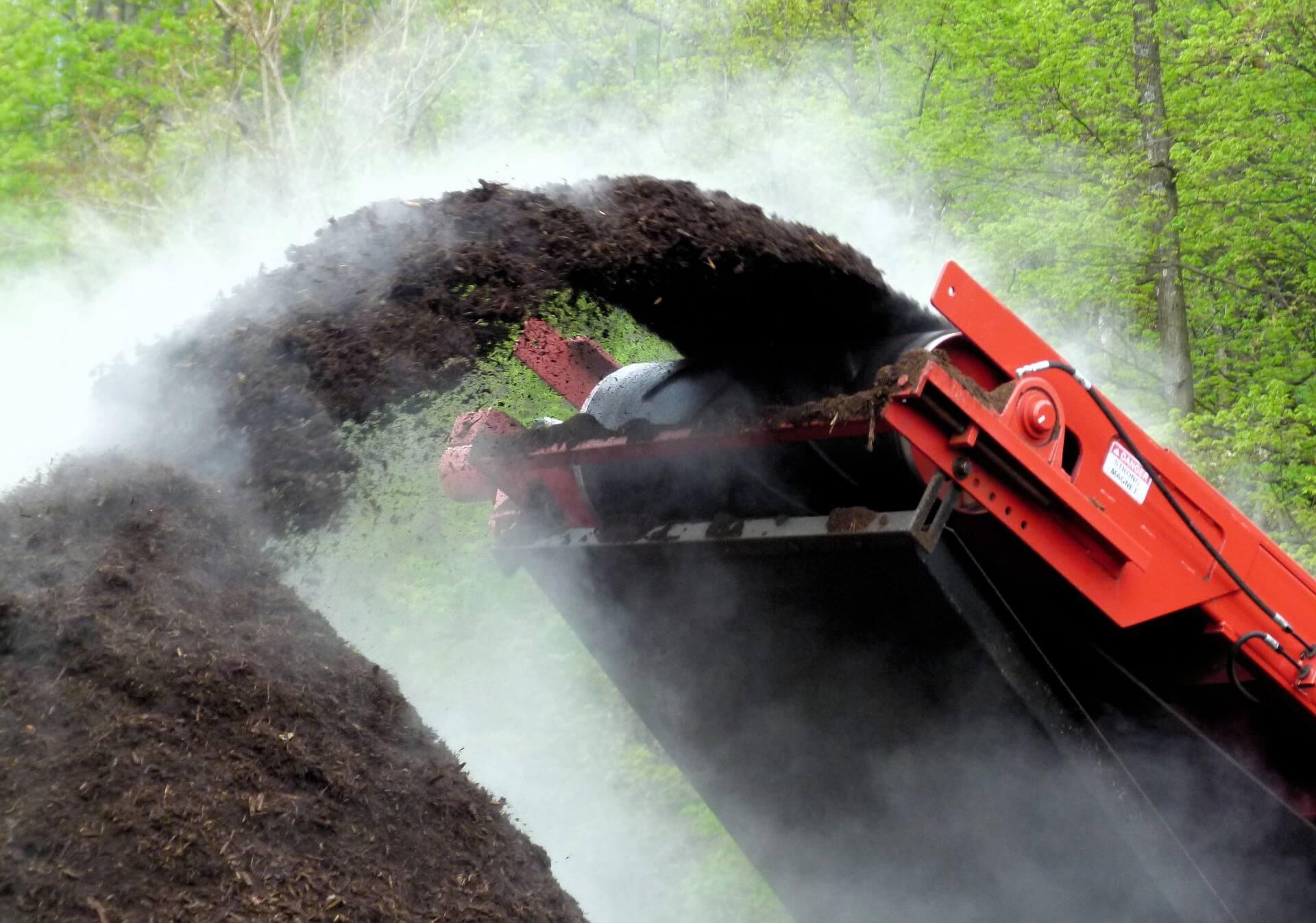 Tas de compost industriel qui se fait remplir par une machine