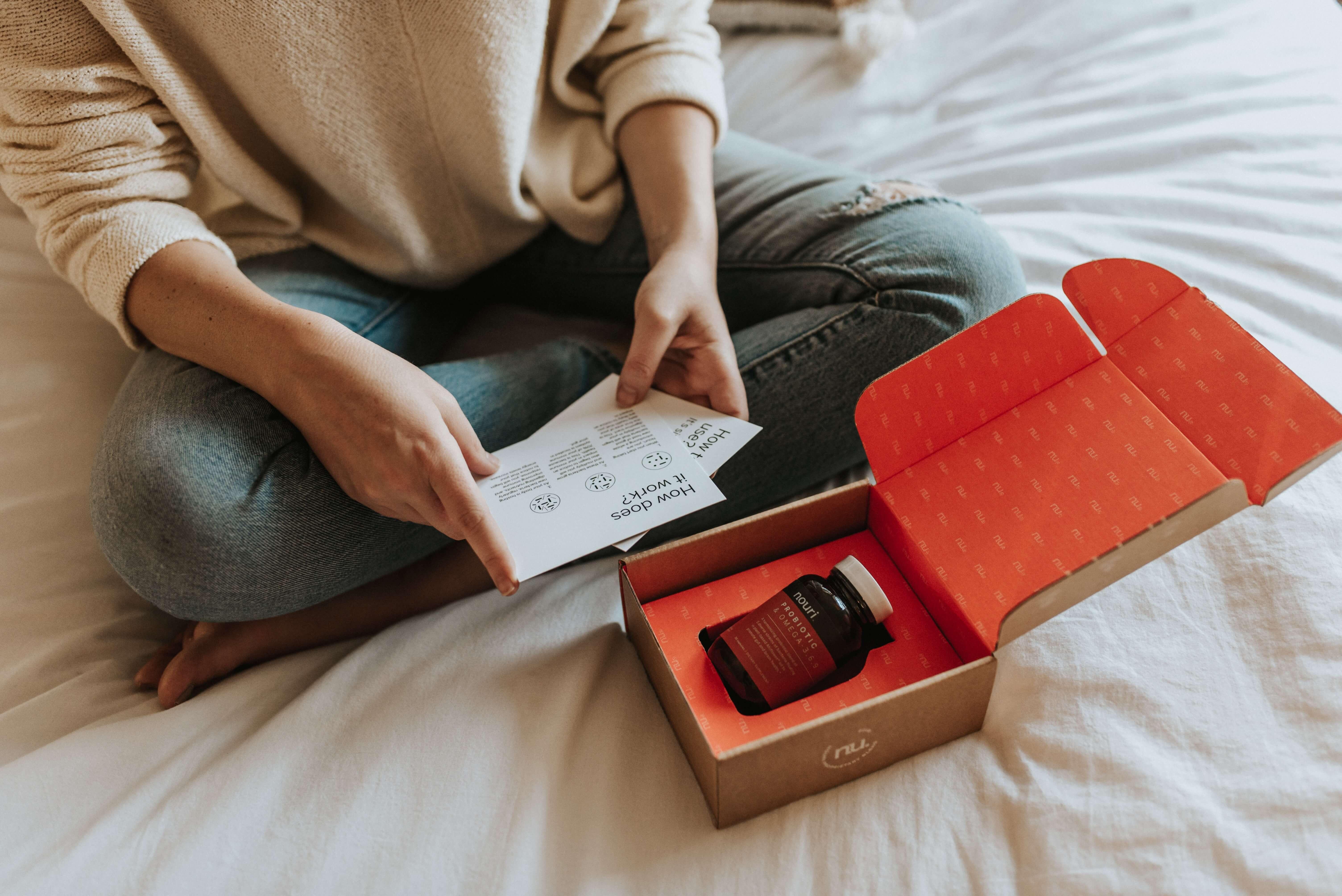 una chica abre una caja postal personalizada