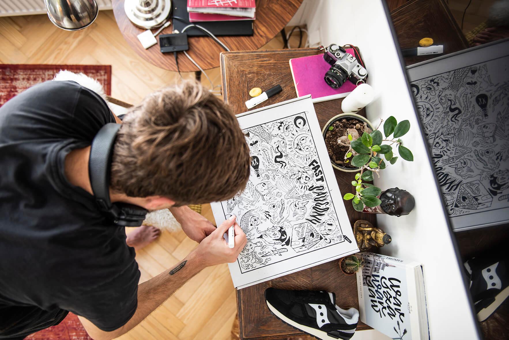 un chico dibuja sobre una caja postal blanca
