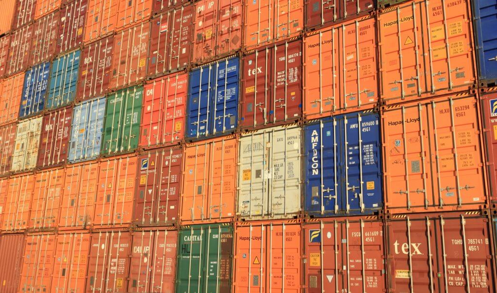 orange, red, green, blue and white shipping containers stacked on top one another