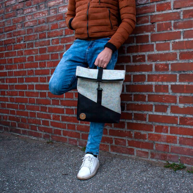 Personne appuyée contre un mur de briques avec un sac à dos en feutre Feeling Felt