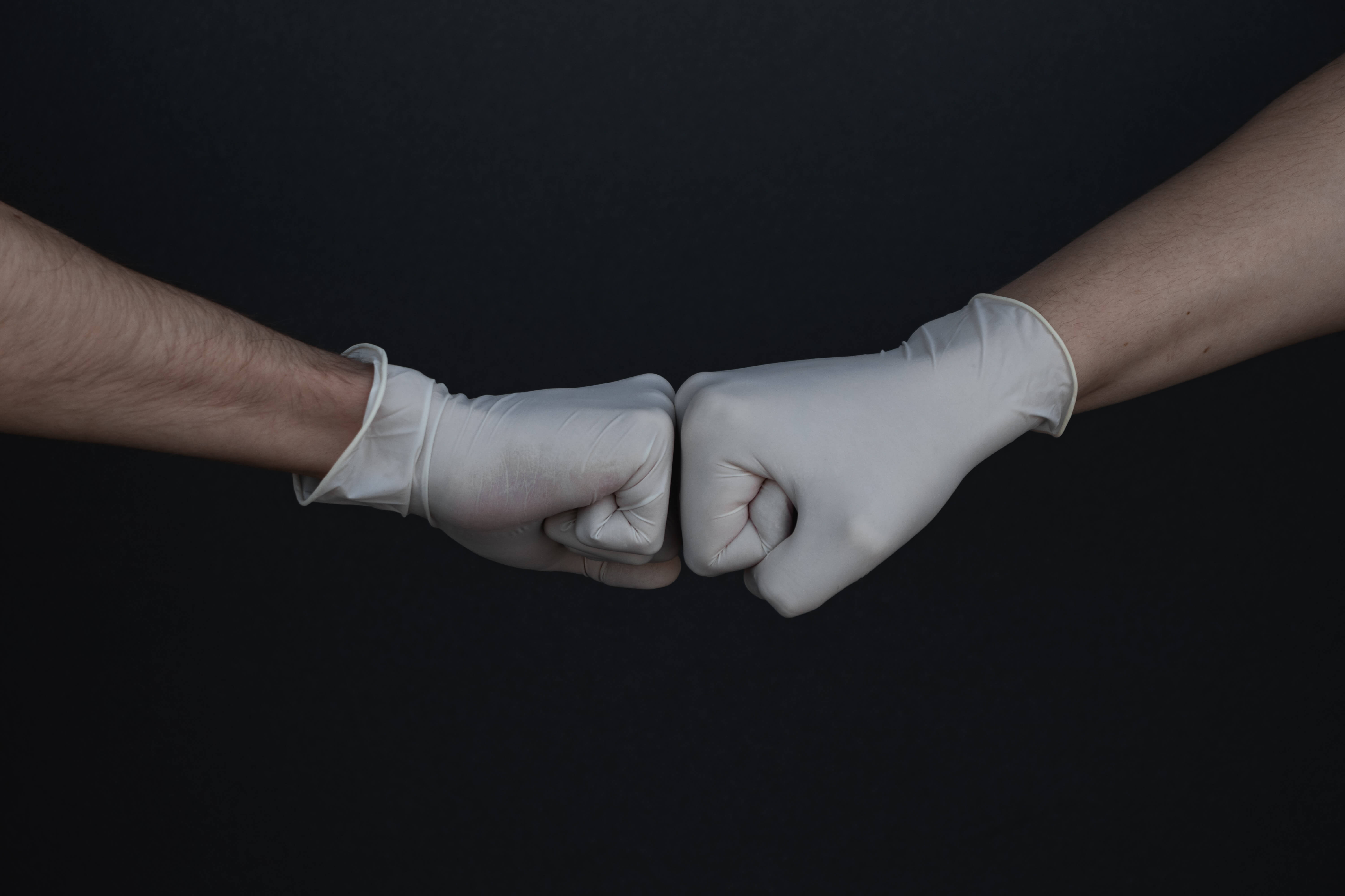 two people fist pumping wearing rubber gloves