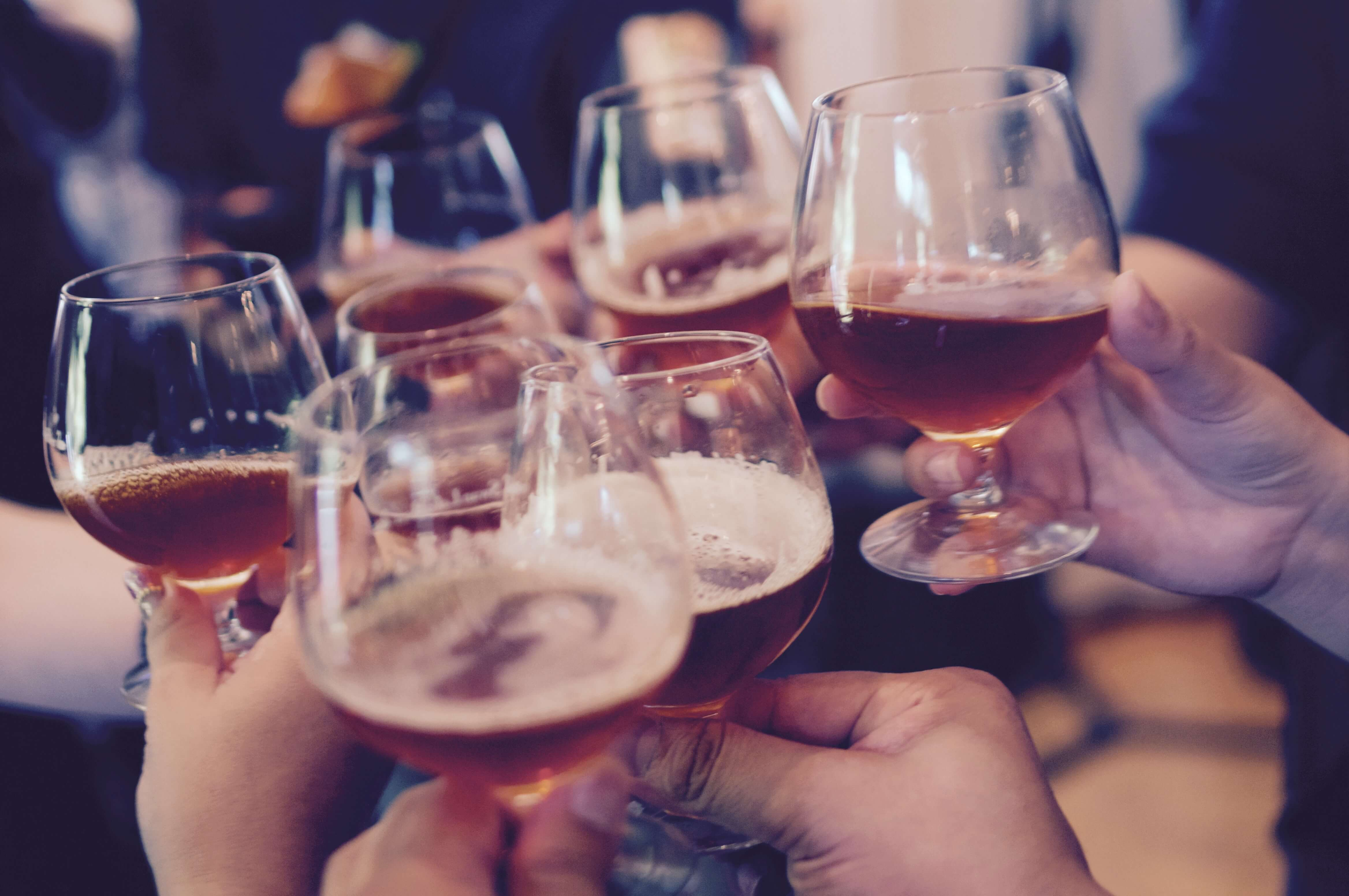 people holding beer glasses toasting