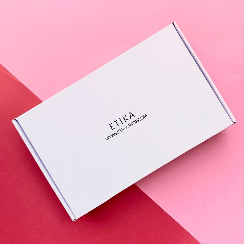 una caja blanca sobre una mesa rosa
