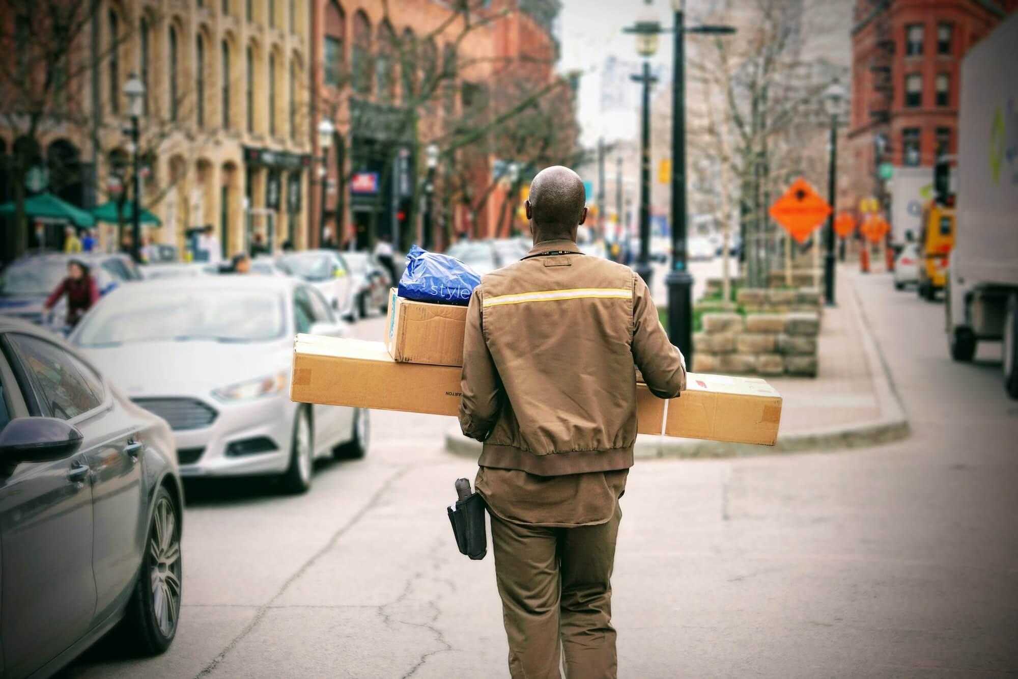 Livreur dans la rue qui tient des cartons