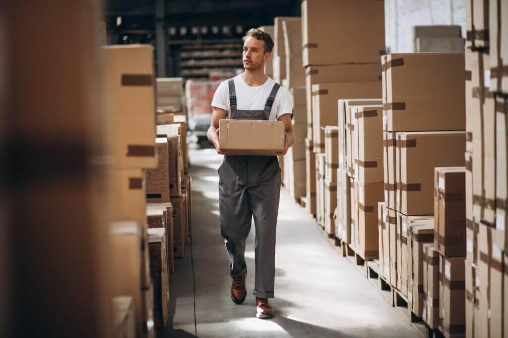 Employé avec un carton dans un entrepôt