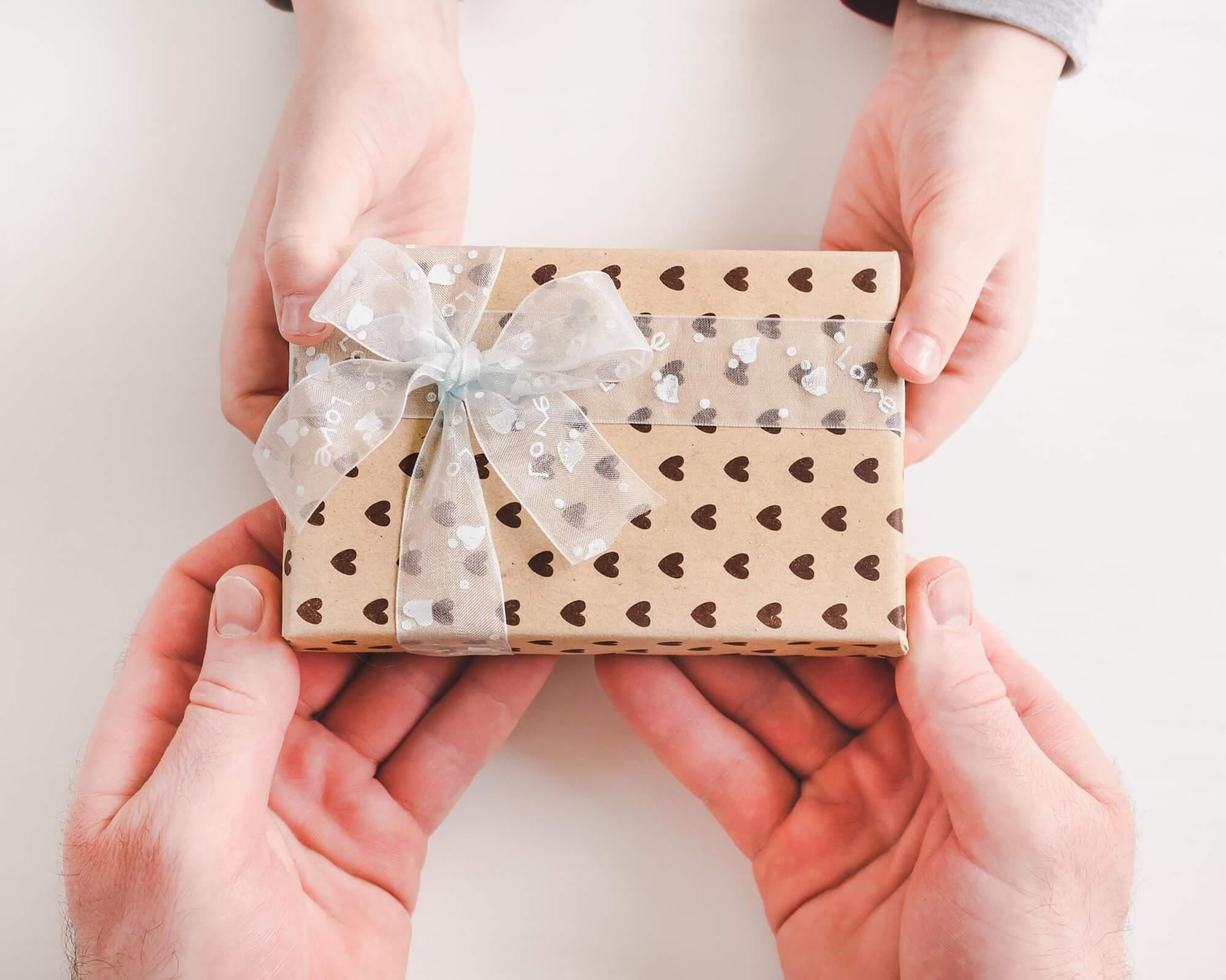 un dependiente entrega un regalo promocional a un cliente