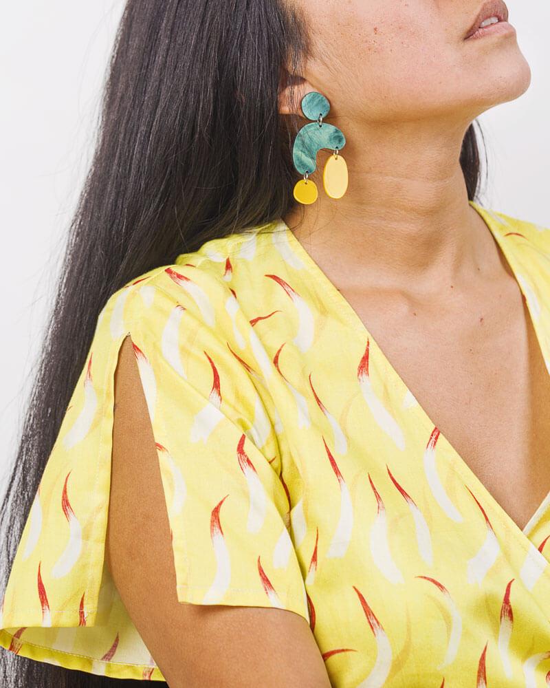 una modelo posa con un vestido amarillo y pendientes a juego