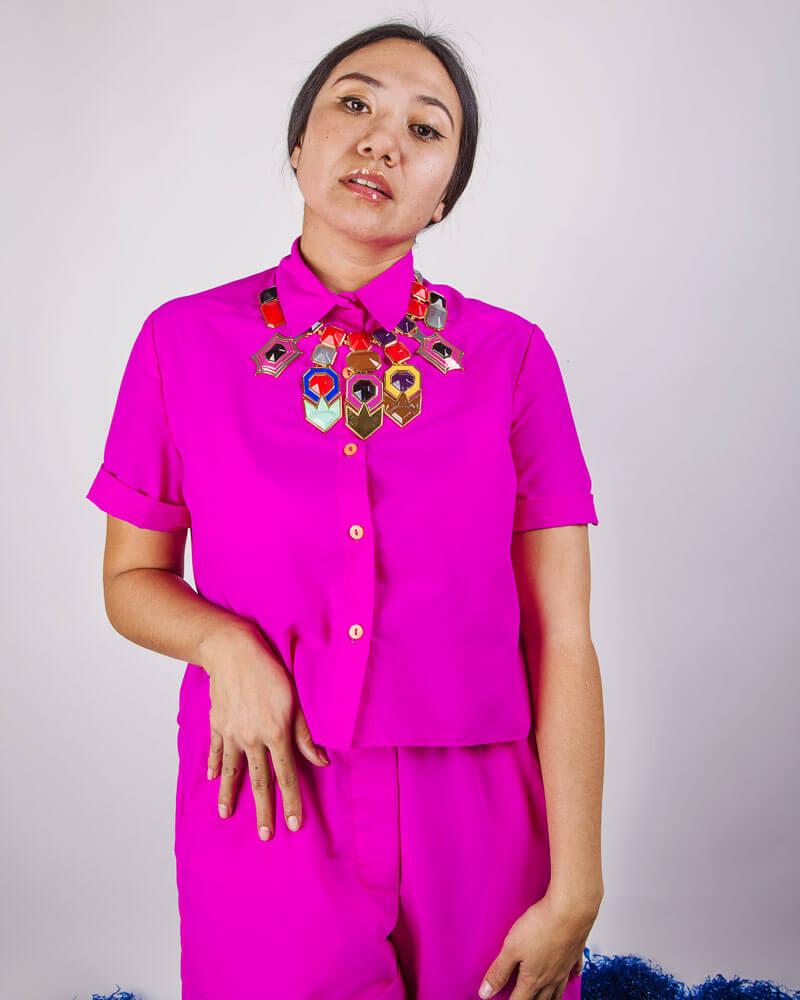 una modelo posa con un conjunto rosa y un collar
