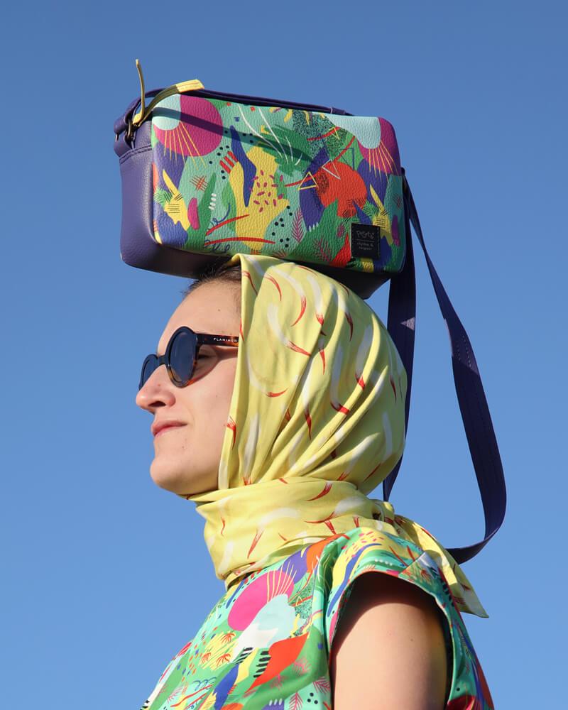 una chica posa con un bolso sobre su cabeza