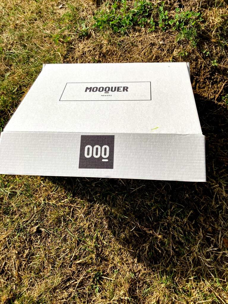 Una caja blanca con el logo MOOQUER