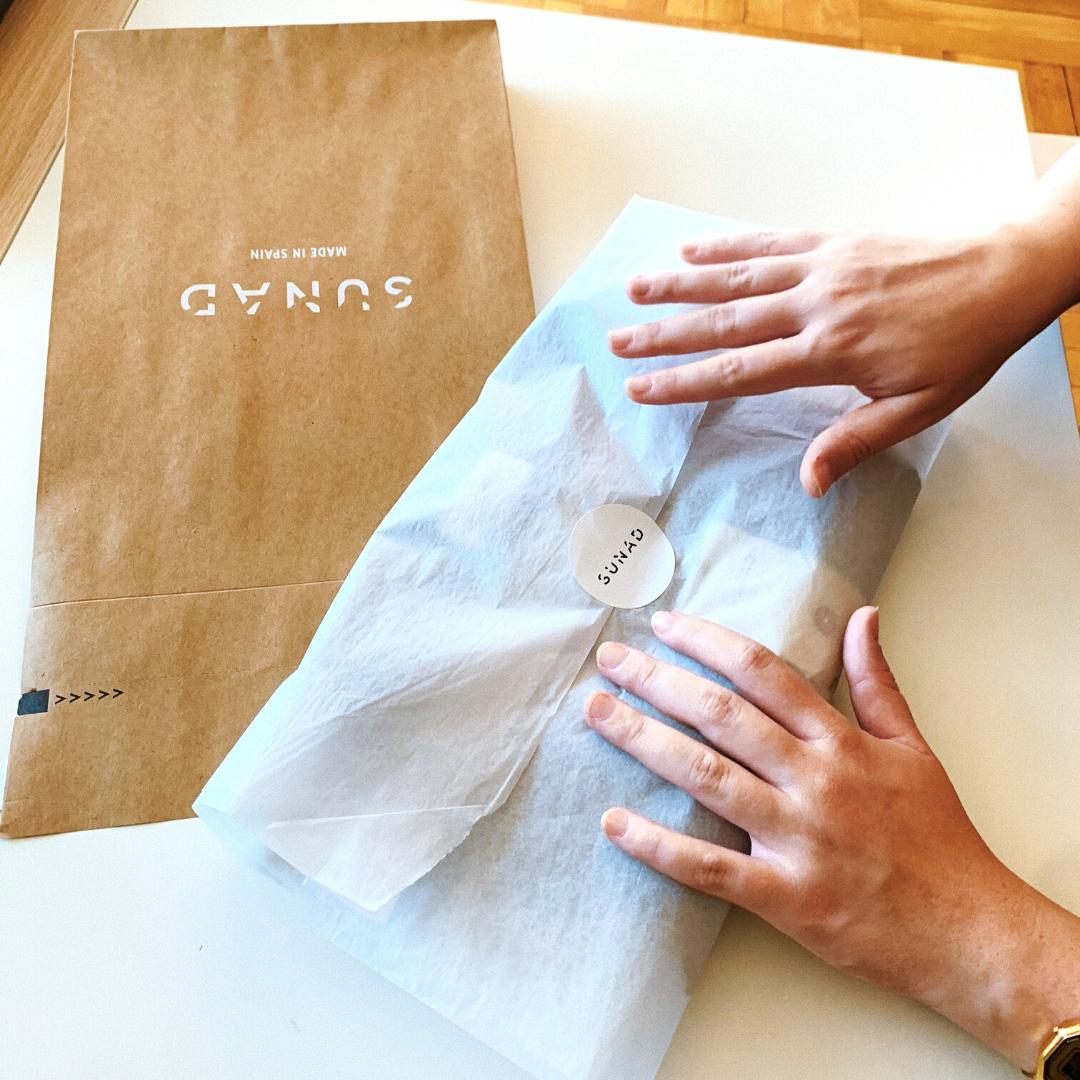 una chica envuelve ropa en papel de seda