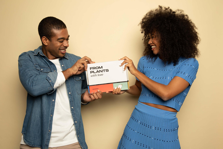 una chica y un chico sostienen una caja colorida