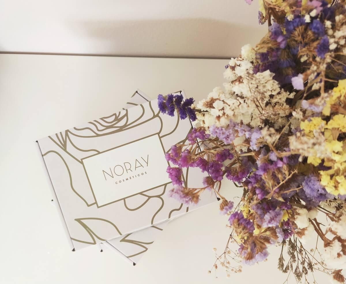 Boîte en carton du packaging de Noray Cosméticos et bouquet de fleurs