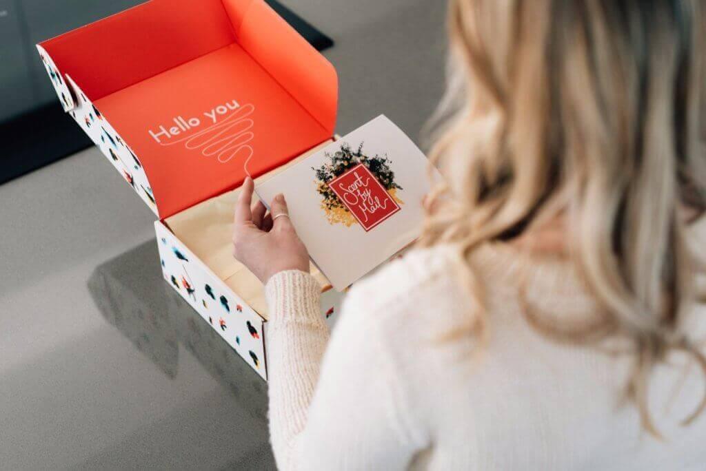 una chica abre una caja de cartón personalizada